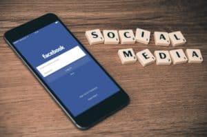cell phone and scrabble tiles spelling Social Media