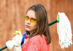 woman wearing goggles holding cleaning supplies
