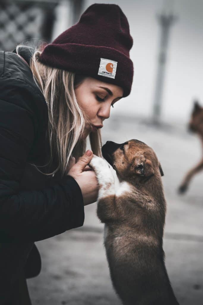 Woman leaning to give a puppy a kiss.